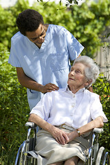 smiling healthcare worker talking to senior handicapped patient