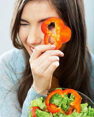 Woman eating green salad . Female model close up face studio is