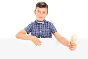 Cute little boy holding an ice cream behind a panel