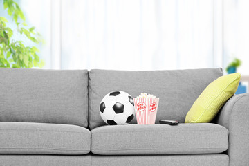 Football and a box of popcorn on a modern sofa
