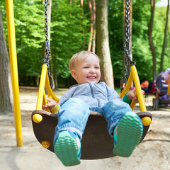 Happy little blond boy having fun on a swing.