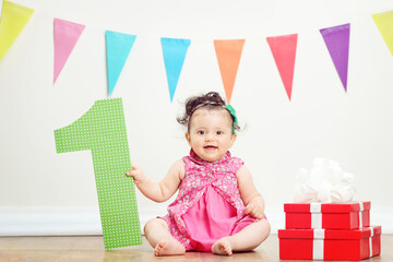 Girl sitting by pile of presents on birthday party