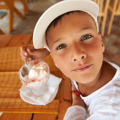 Young boy eating a tasty ice cream outdoor.