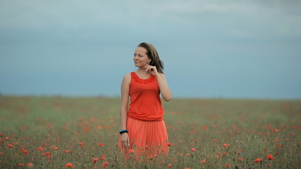 Beautiful Girl in red dress among the poppy field