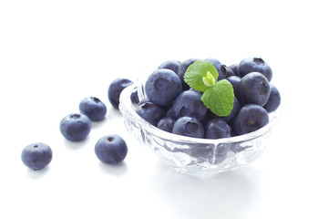Beautiful fresh blueberries in a white bowl on a white backgroun