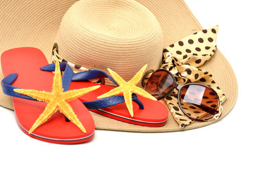 red flip flops with starfishes, sunglasses and a seashell