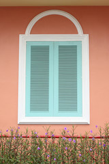 pastel blue window with white frame on pink wall