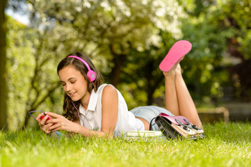 Summer girl lying grass listen music headphones