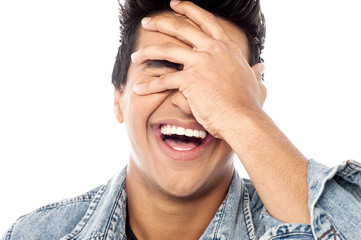 Laughing young man with hand on his face