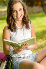 Cheerful student girl sitting grass read book