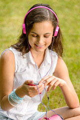 Teenage girl with headphones sitting on grass