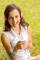 Laughing teenage girl listen music sitting grass