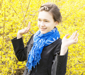 girl in a blue scarf around a flowering bush