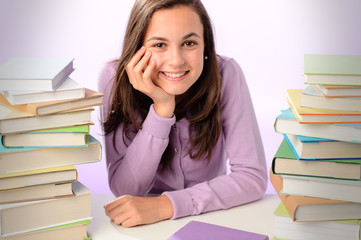 Smiling student girl between stacks of books