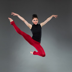 Female dancer jumping with arms outstretched.