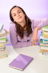 Confident student girl between stacks of books