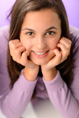 Teenage girl smiling on purple close-up portrait