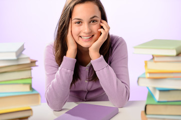 Smiling student girl between piles of books