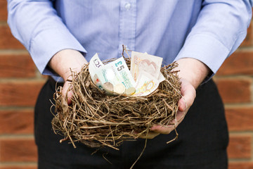 Man holding nest of money, horizontal