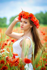 Beautiful young woman in red bright poppy field. Summer portrait