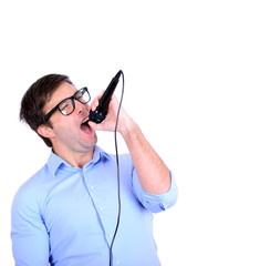 Portrait of handsome young man singing on microphone isolated o