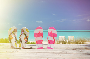 Two pairs of flip-flops against Atlantic. Exuma, Bahamas