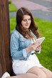 brunette woman sitting on grass at park and using tablet