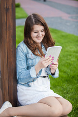 brunette student reading book on tablet at park on grass
