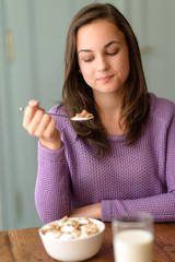 Young woman eating healthy cereal breakfast
