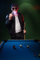 Man playing pool in a club smoking a cigarette