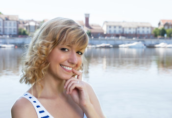 Young woman on a river laughing at camera