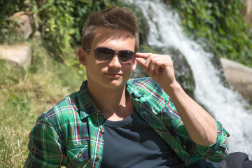 Guy in sunglasses resting in nature near the waterfall