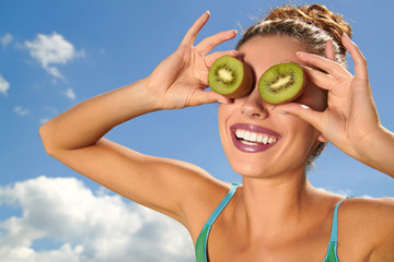 Happy young woman holding kiwi in front of her eyes over sky bac