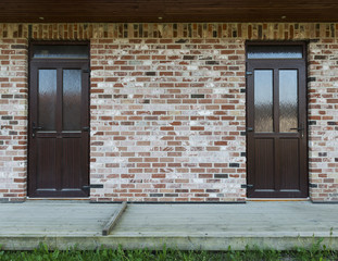 Brick wall with two doors, wooden terrace and grass