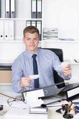 Junger verwirrter Mann hält mehrere Zettel in der Hand