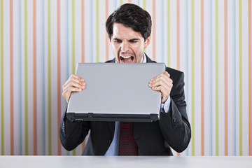 Businessman eating laptop