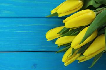 żółte tulipany na niebieskich deskach