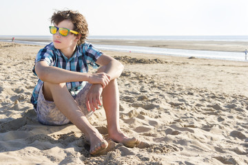 Teenage boy sitting on the beach