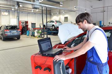 Auto-Mechaniker mit Diagnosegerät in Werkstatt