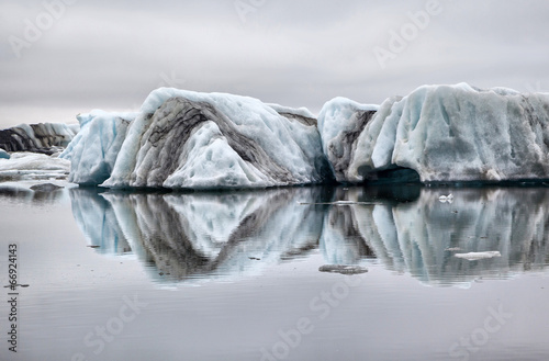 Floating ice symmetrically reflected in the water - 66924143