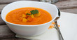 A plate of carrot soup with fresh pasley