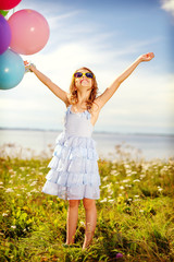 happy girl waving hands with colorful balloons