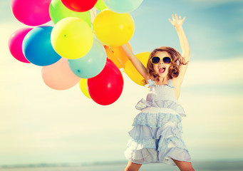 happy jumping girl with colorful balloons