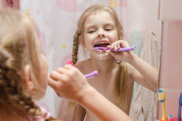 Five-year girl brushing her teeth in bathroom