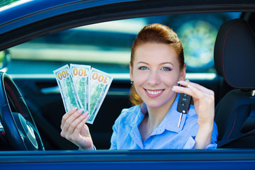 Woman showing car keys, dollar bills, sitting in new car