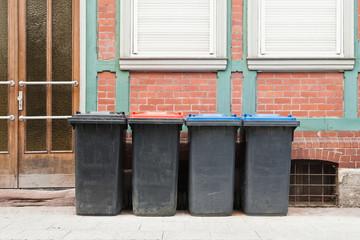 Vier Mülltonnen mit verschiedenen Deckelfarben vor einem Haus