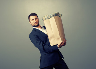 businessman holding heavy paper bag