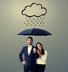 smiley young couple with black umbrella