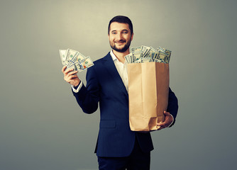 successful businessman holding paper bag