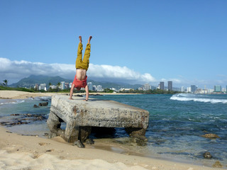 Man Handstands on old pillbox on beach with the City of Honolulu
